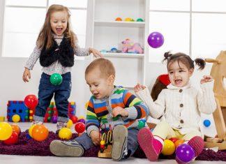 Troje dzieci wykonują zabawy ruchowe w żłobku